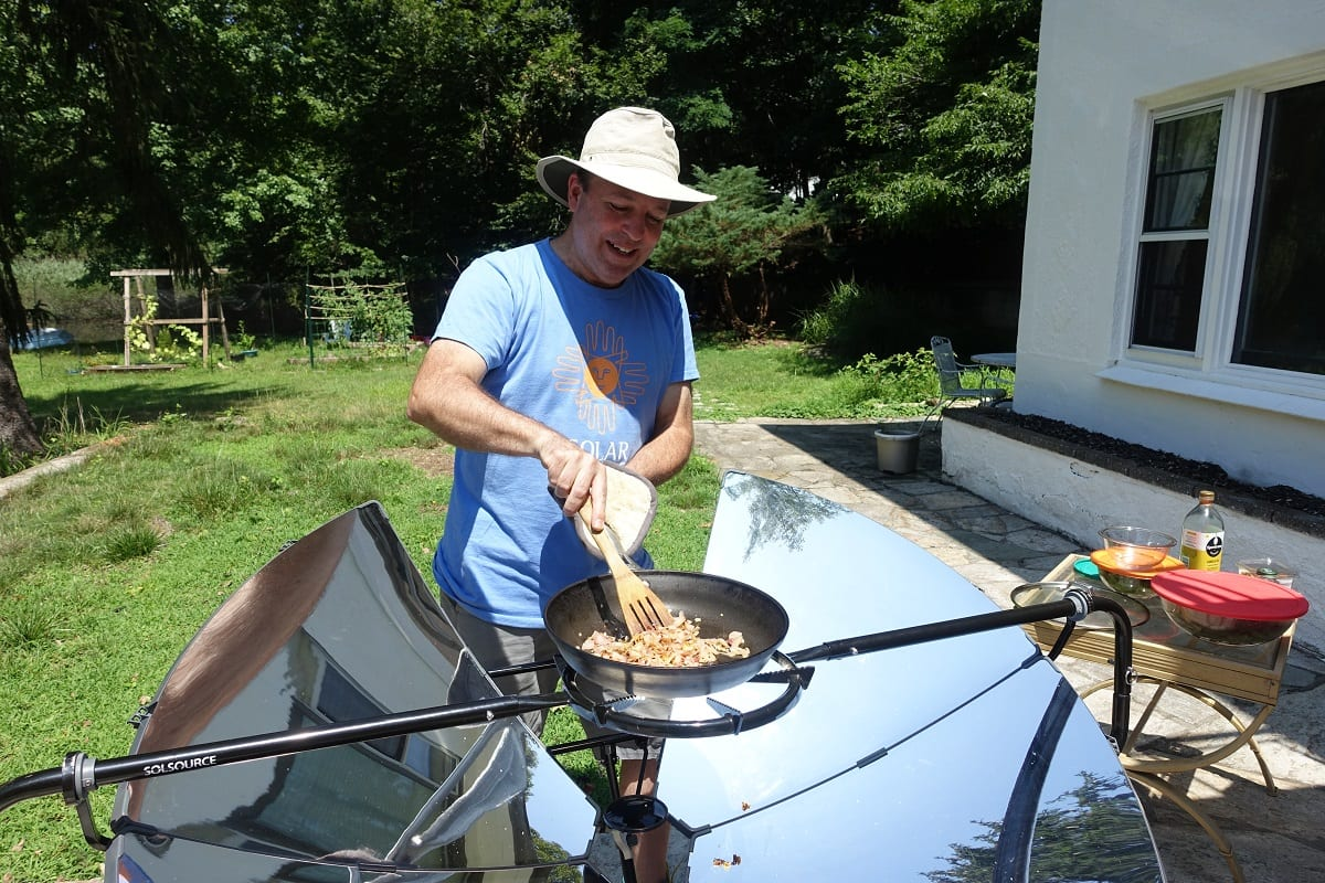 man-cooking-food-on-solar-cooking-device
